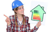 Craftswoman holding an energy consumption label — Stock Photo