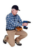 Grey haired man with drill — Stock Photo
