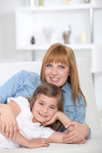 A 35 years old mother and her little girl lying down on a couch — Stock Photo