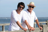 Father and son stood by waterfront — Stockfoto
