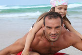 A little girl and her father playing on the beach — Stock Photo