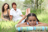 Little girl relaxing in park with mother and grandma in background — Stock Photo