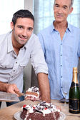 Two men cutting celebration cake — Stock Photo