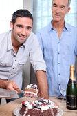 Two men cutting celebration cake — Stock Photo