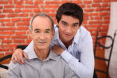 A teenager and his grandfather posing in a restaurant — Stock Photo
