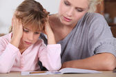 Mother helping her daughter with her homework. — Stock Photo