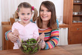 Mother and daughter preparing a salad — Stock Photo