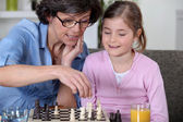 A mother and her daughter playing chess. — Stock Photo