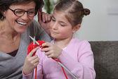 Een moeder die haar dochter onderwijzen hoe te breien. — Stockfoto