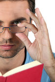 Closeup of a man in glasses reading a book — Stock Photo