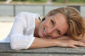 Closeup of a smiling woman sitting outdoors — Stock Photo