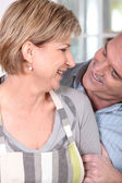 Couple in their fifties laughing in the kitchen — Stock Photo
