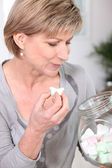 Woman eating marshmallows straight out of a jar — Stock Photo