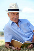 Senior reading a book in the park — Stock Photo