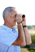 Senior man looking through binoculars — Stock Photo