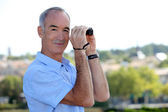 Mature man with binoculars. — Stock Photo