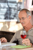 Grey haired man using laptop whilst drinking glass of wine — Stock Photo