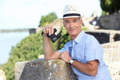 Older male tourist with binoculars leaning on the citadel walls at Blaye in — Stock Photo