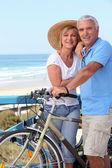 älteres paar mit fahrrädern an einem strand — Stockfoto