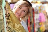 Senior woman in a textile shop — Stock Photo