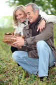 Old couple watching a wickerwork basket of mushrooms in the countryside — Stock Photo