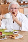 Oude dame ontbijten in de keuken — Stockfoto