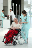 Nurse with an elderly lady in a wheelchair — Stock Photo