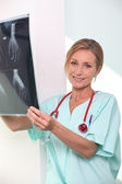 Nurse looking at X-ray — Stock Photo