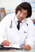 Handsome hospital doctor writing in a personal organizer — Stock Photo