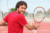 Smiling man holding racquet by fence of municipal tennis court — Stock Photo