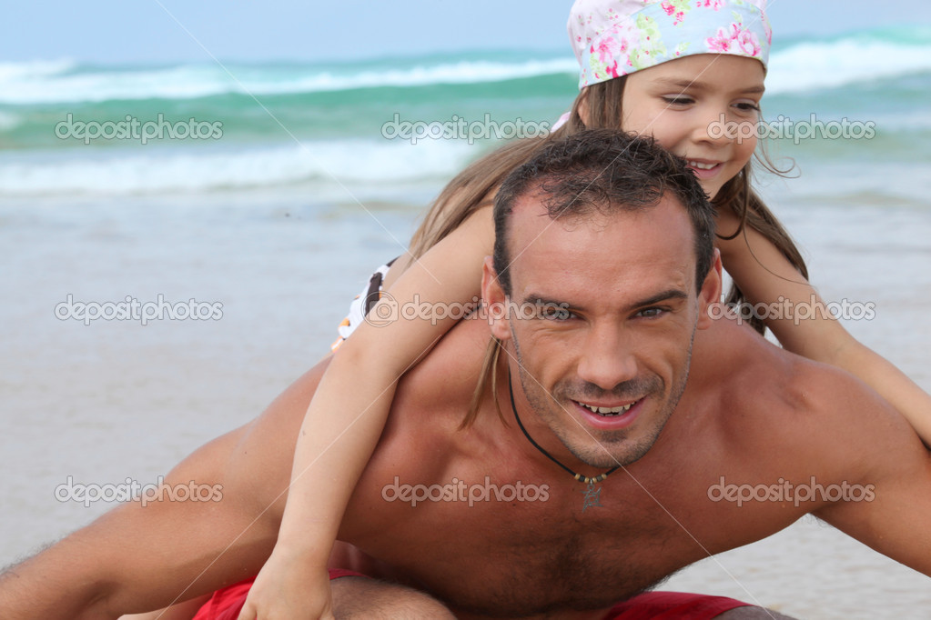 A little girl and her father playing on the beach — Stock Photo #7933675