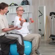 Older woman working out with a personal trainer at the gym — Stock Photo #7940355