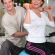 Mature woman and trainer in workout — Stock Photo