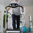 Middle-aged man on treadmill at home — Stock Photo