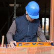 Stock Photo: Bricklayer taking measurements