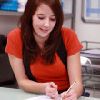 Red-haired girl sitting at desk — Stock Photo