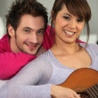 Young couple with a guitar at home — Stock Photo #7944230