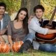 Three musicians at the foot of a tree — Stock Photo
