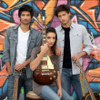 Three guitarists behind tagged wall — Stock Photo #7944815