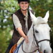 Young horsewoman with white horse — Stockfoto