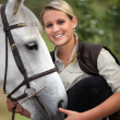 Blond teenage girl with horse - Stock Photo