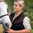 Young lady stroking her horse — Stock Photo