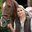 Stock Photo: Young blonde womand horse in front of stable