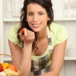 Woman eating tomato in kitchen — Stock Photo #7945608