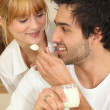 Man feeding his girlfriend yogurt - Stock Photo