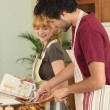 Couple preparing a meal together with the help of a cookbook - Stock Photo