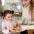 Stock Photo: Mum and daughter making pancakes