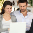 Couple using laptop in living room — Stock Photo #7946868