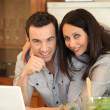 Couple in kitchen on laptop — Stock Photo