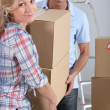 Couple moving in carrying cartons — Stock Photo